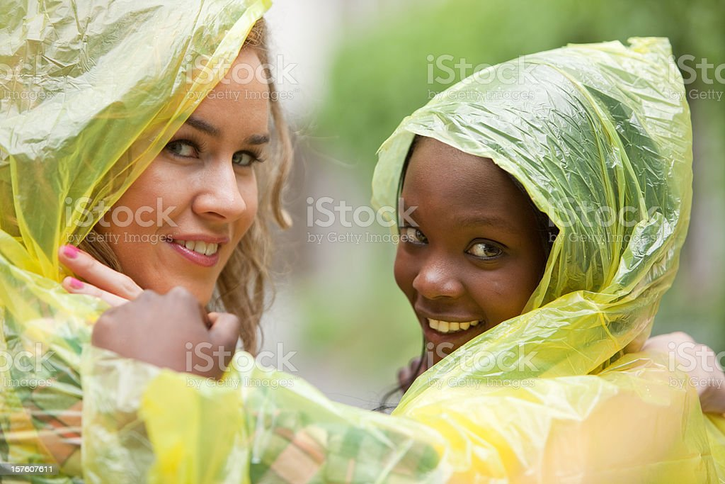 Two friends in raincoats smiling stock photo
