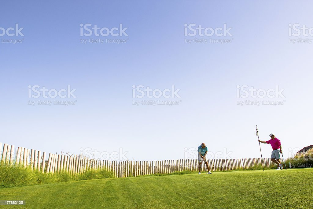 Two friends in the putting green royalty-free stock photo