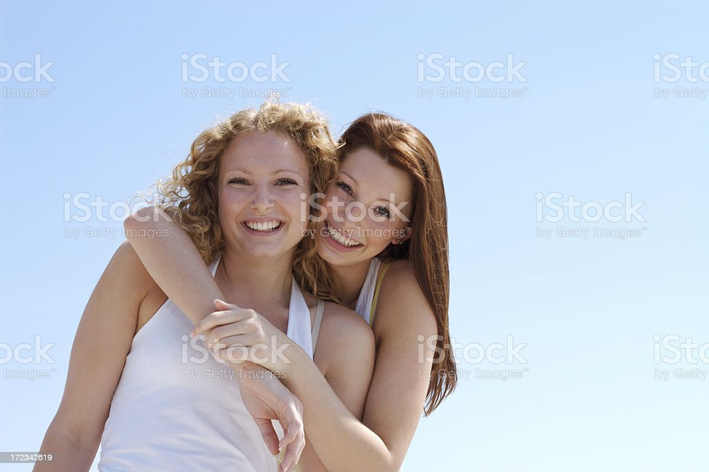 Two friends in white tank tops hugging with blue background royalty-free stock photo