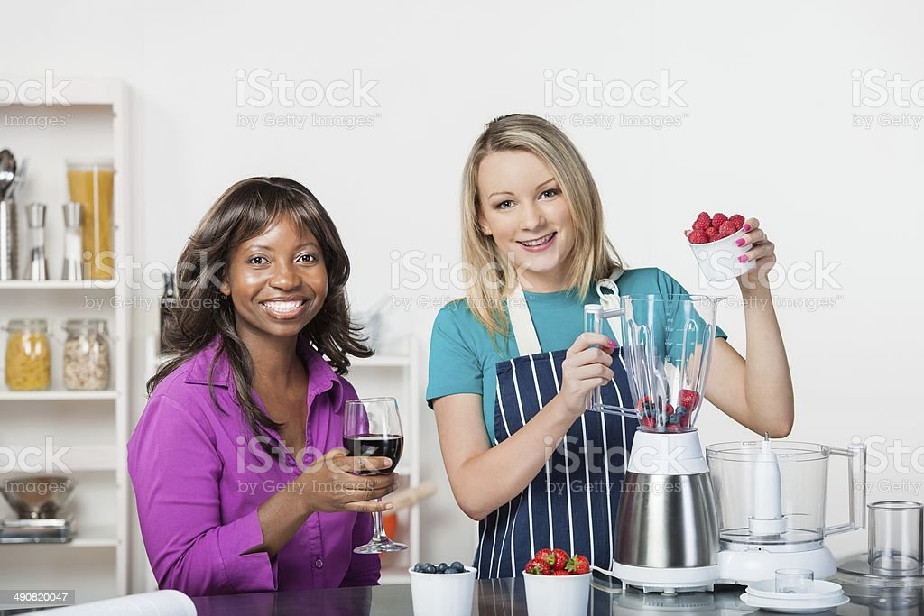 Two Friends Interacting While Preparing Healthy  Dessert In A Kitchen royalty-free stock photo