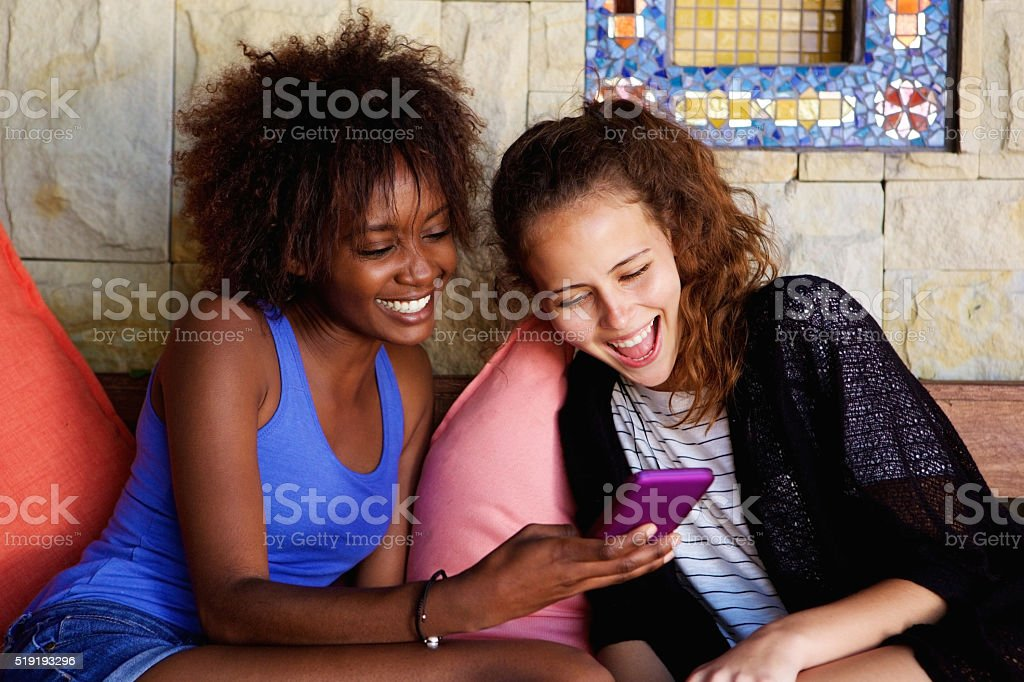 Two friends laughing and looking at mobile phone stock photo