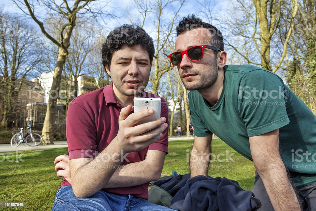 Two friends looking at a smart phone stock photo