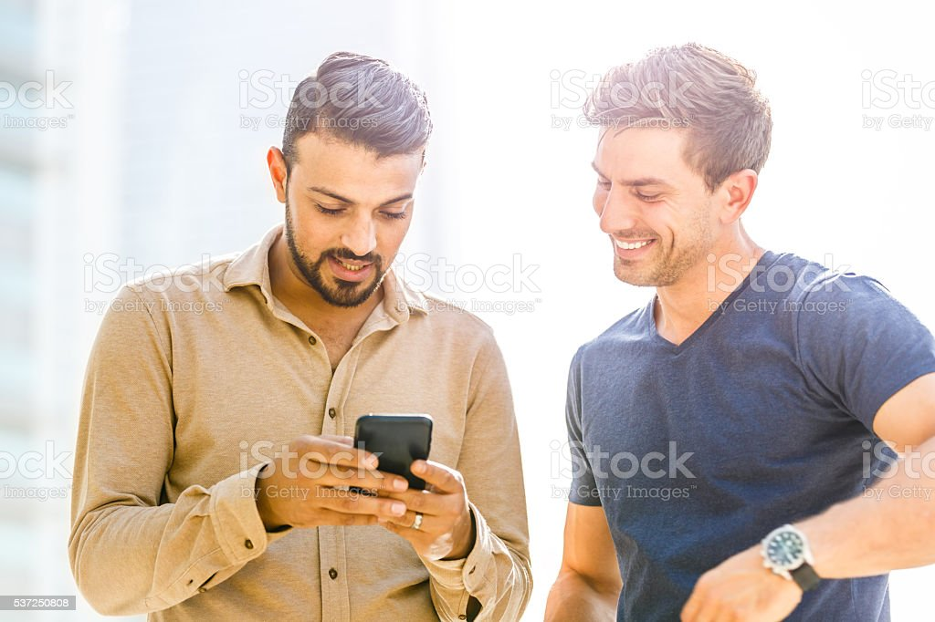 Two friends looking at smart phone stock photo