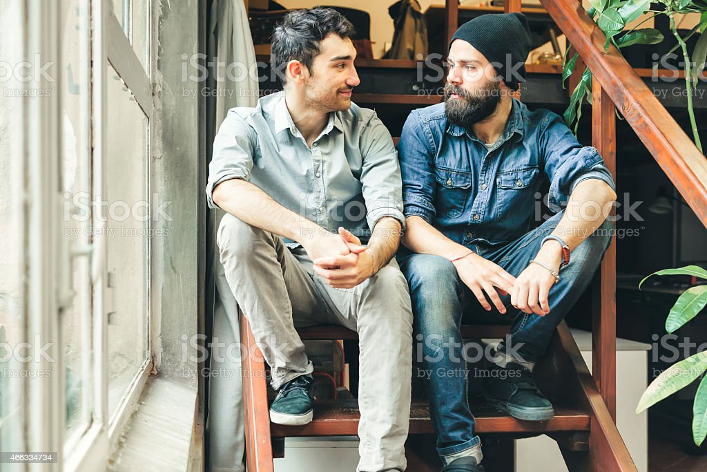 Two friends looking each other sitting on stairs stock photo