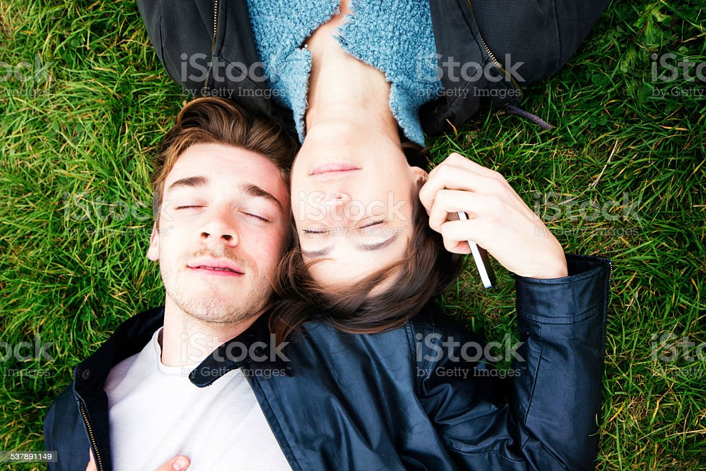Two friends lying down listening to music on mobile phone stock photo
