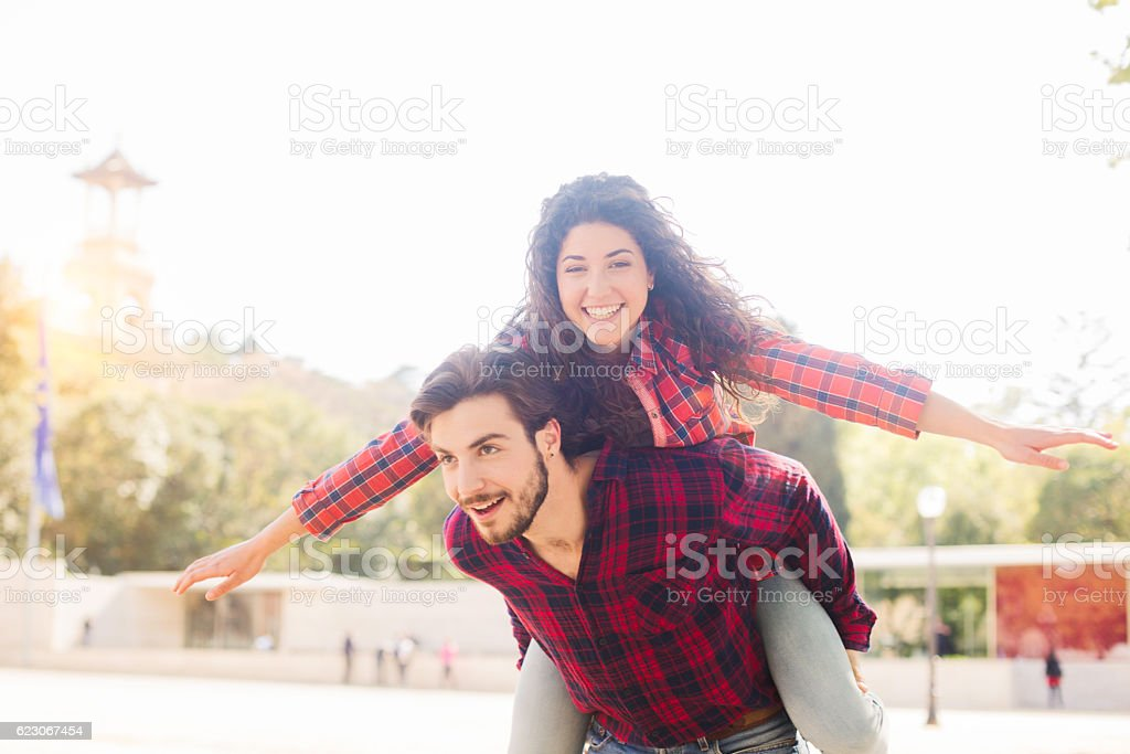 Two friends meet in Barcelona and do a piggyback. stock photo
