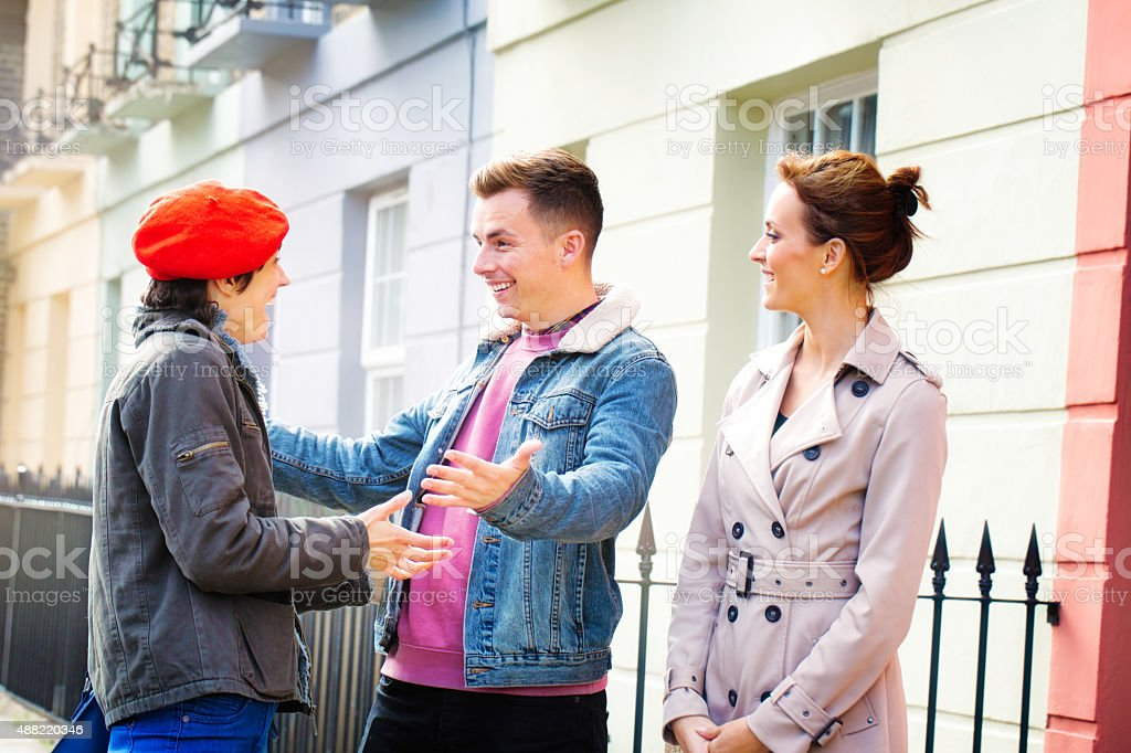 Two friends meet on the street in front of girlfriend stock photo