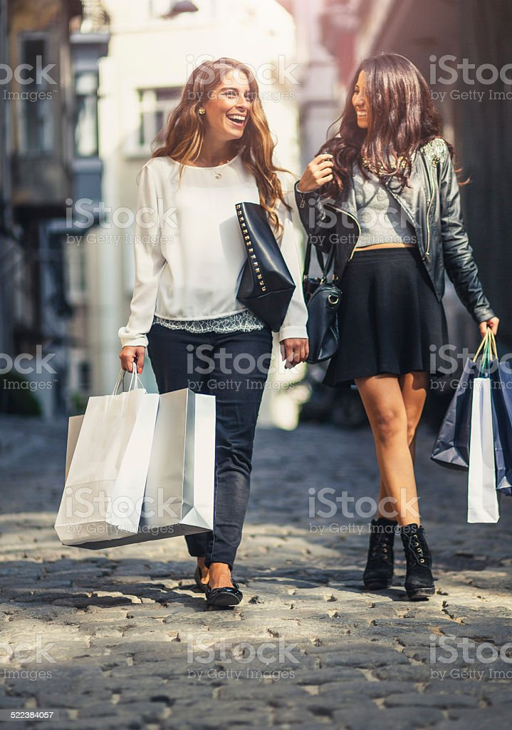 Two friends on the street with shopping bags stock photo