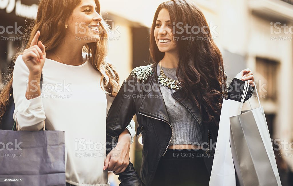 Two friends ont the street with shopping bags stock photo