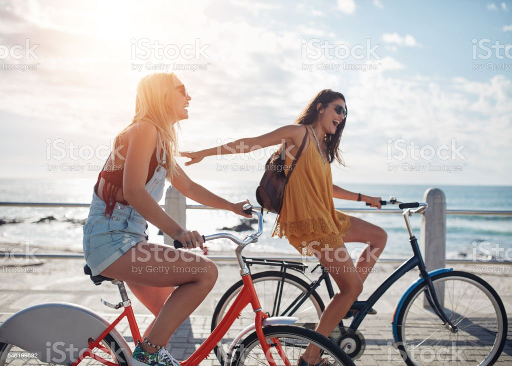 Two friends out for a bike ride on seaside promenade stock photo