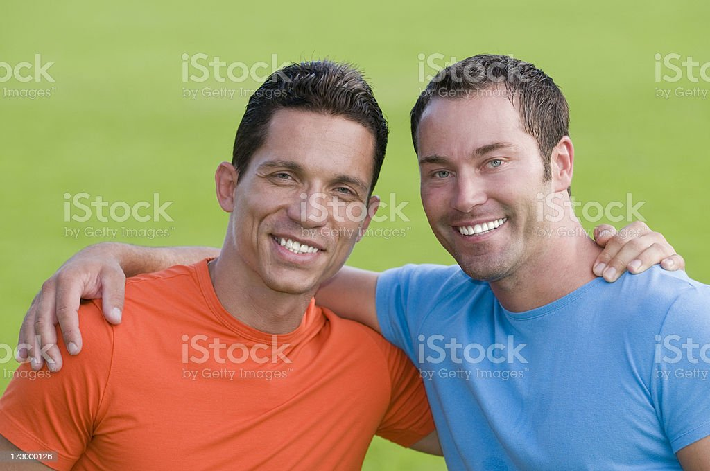 Two Friends Pictured Smiling, Arms Around Shoulders royalty-free stock photo