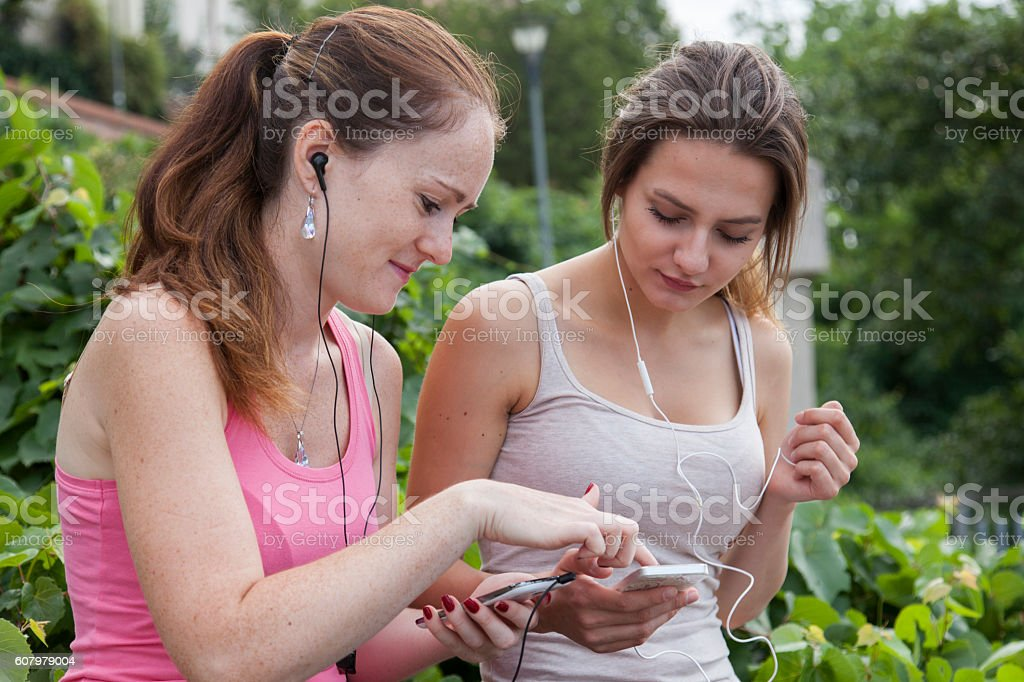 two friends programming their running apps stock photo