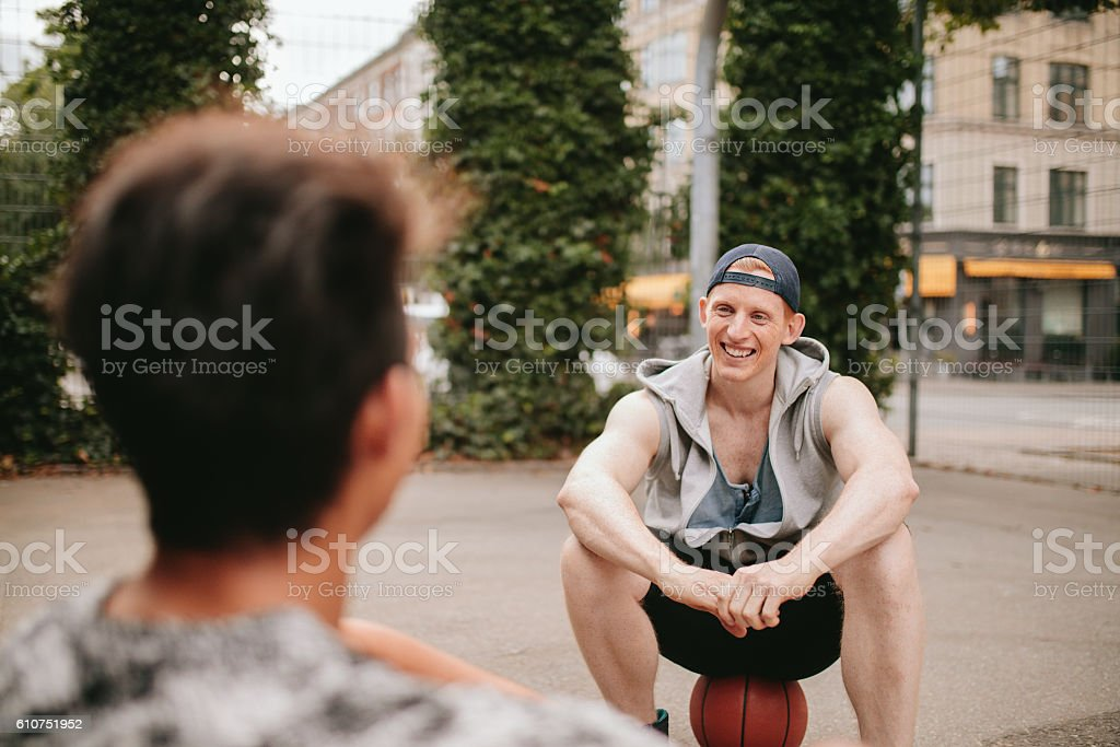 Two friends relaxing after playing basketball on court stock photo