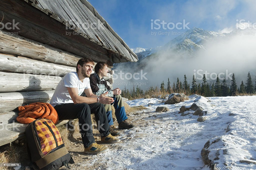 Two friends relaxing on wooden bench in winter mountains outdoors stock photo