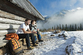 Two friends relaxing on wooden bench in winter mountains outdoors