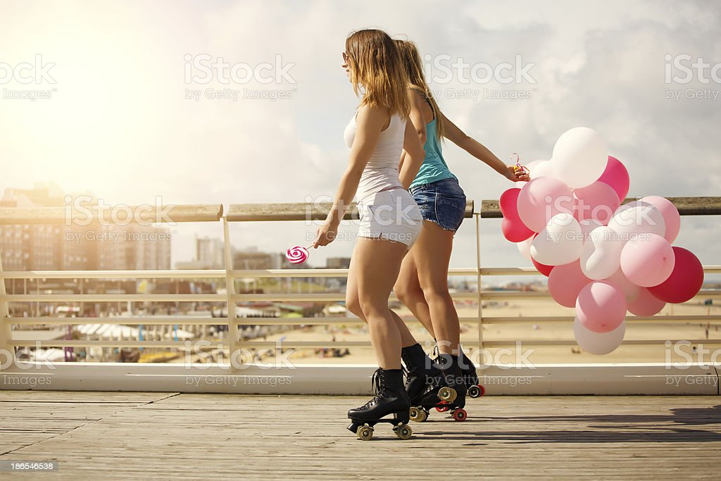 two friends roller skating outdoors royalty-free stock photo