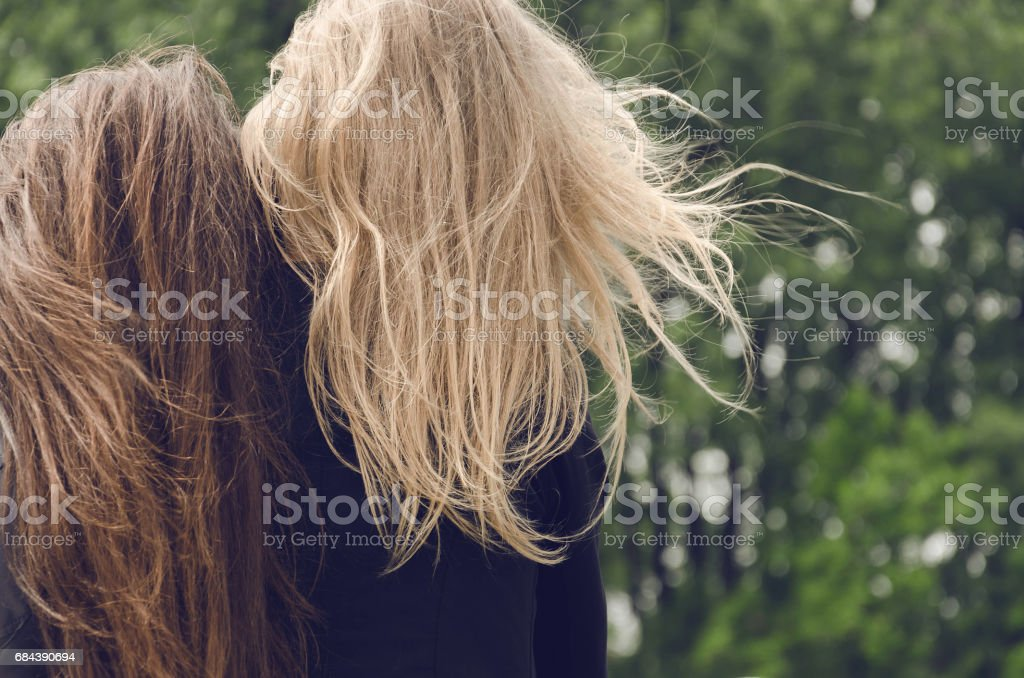 two friends sitting in nature from behind or from the back stock photo
