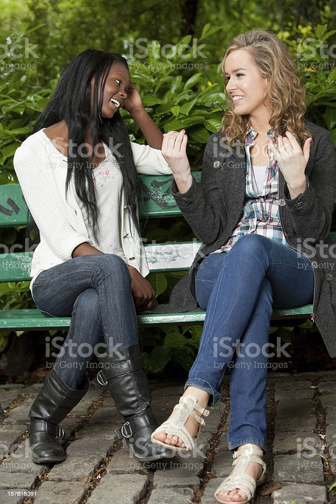 Two friends sitting on a park bench chatting away royalty-free stock photo