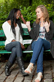 Two friends sitting on a park bench chatting away