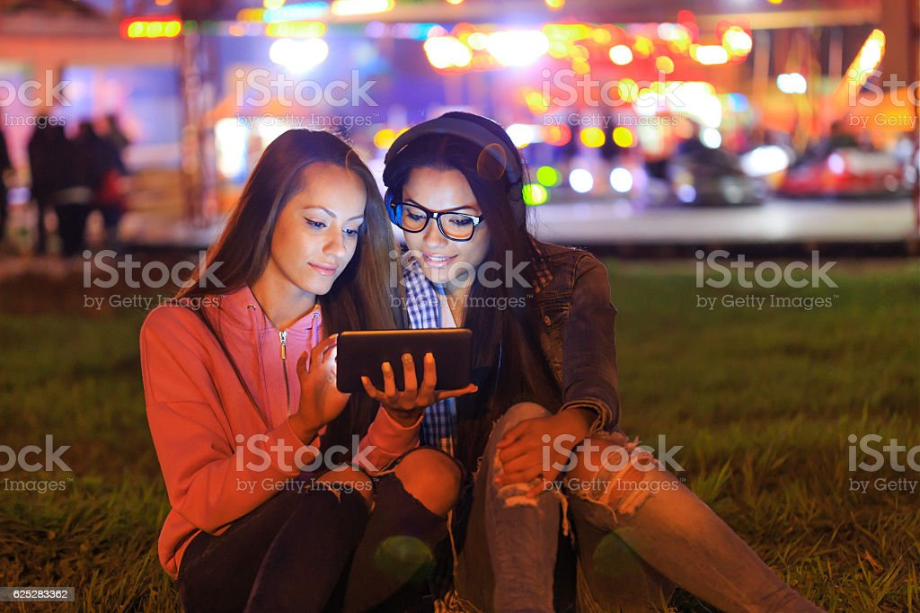 Two friends sitting on grass using digital tablet stock photo
