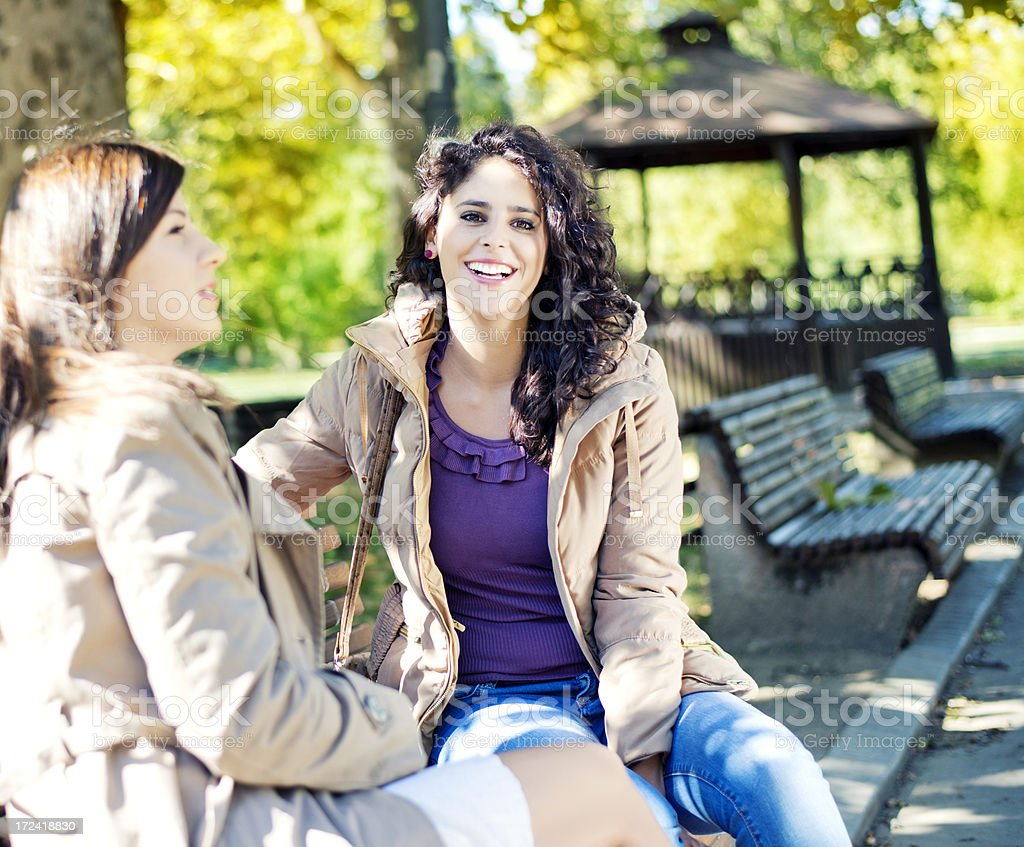 Two friends sitting on the bench in park. royalty-free stock photo