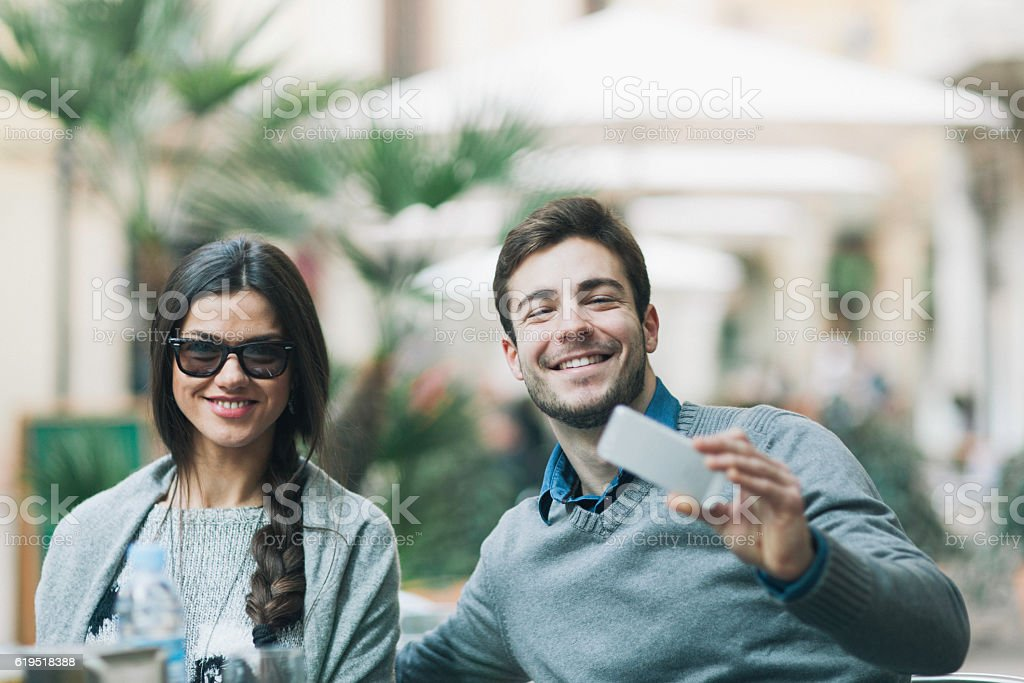 Two friends smiling at camera and making a selfie. stock photo
