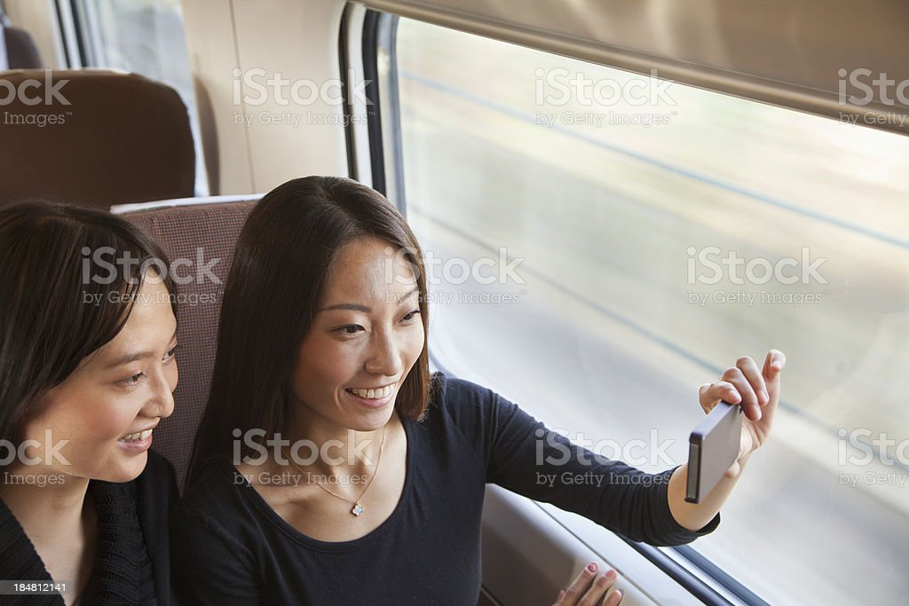 Two Friends Taking a Picture Out the Train Window royalty-free stock photo