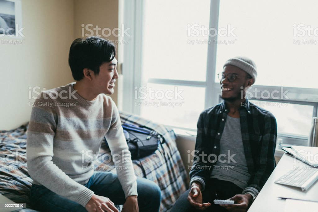 Two friends talking in a dorm room stock photo