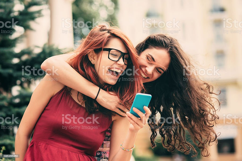 Two friends texting outdoor stock photo