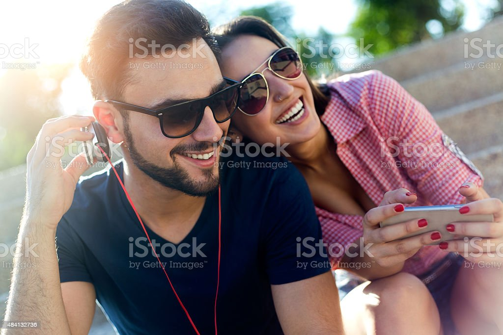 Two friends using mobile phone in the street. stock photo