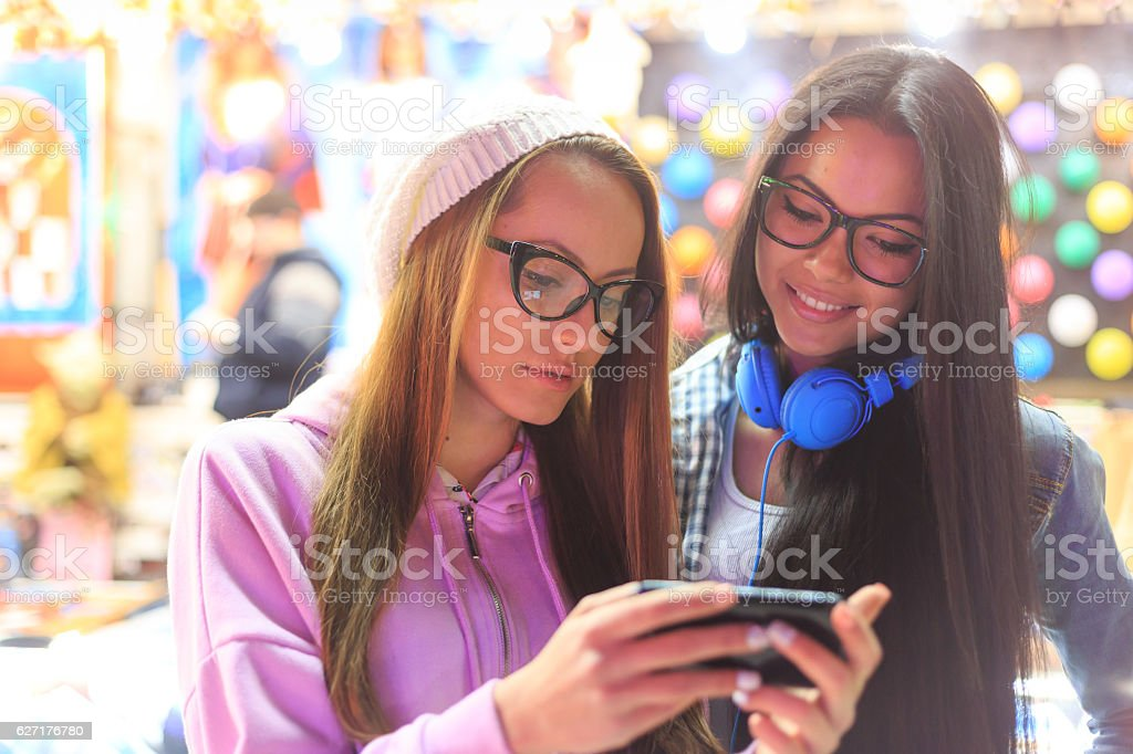 Two friends using smart phone in amusement park stock photo