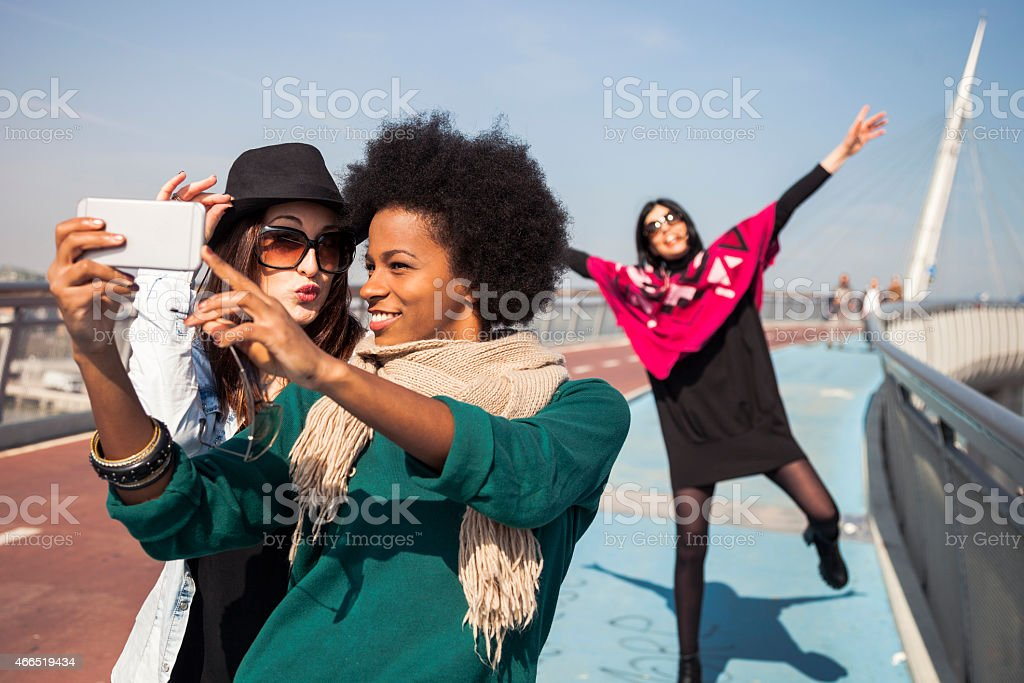 Two friends victim of 'photo bombing' taking a selfie stock photo