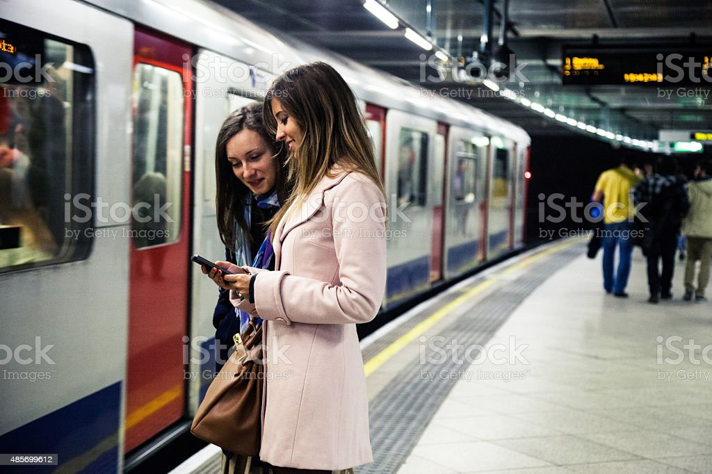 Two friends waiting for the train in the subway platform stock photo