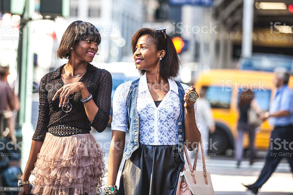 Two friends walking down the streets stock photo