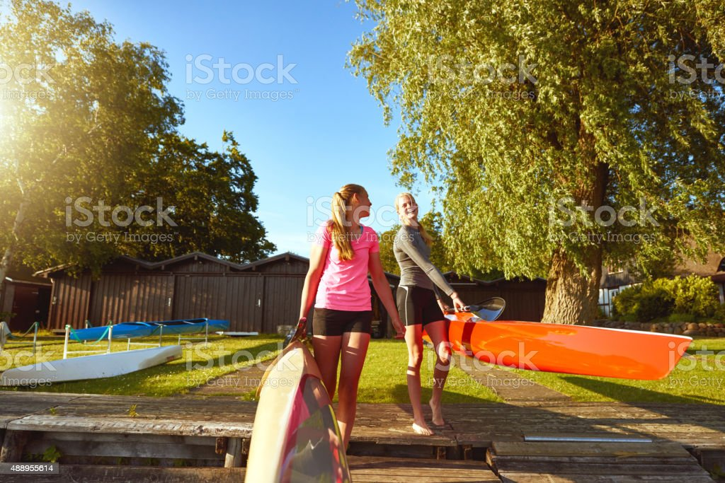 Two friends with kayaks stock photo