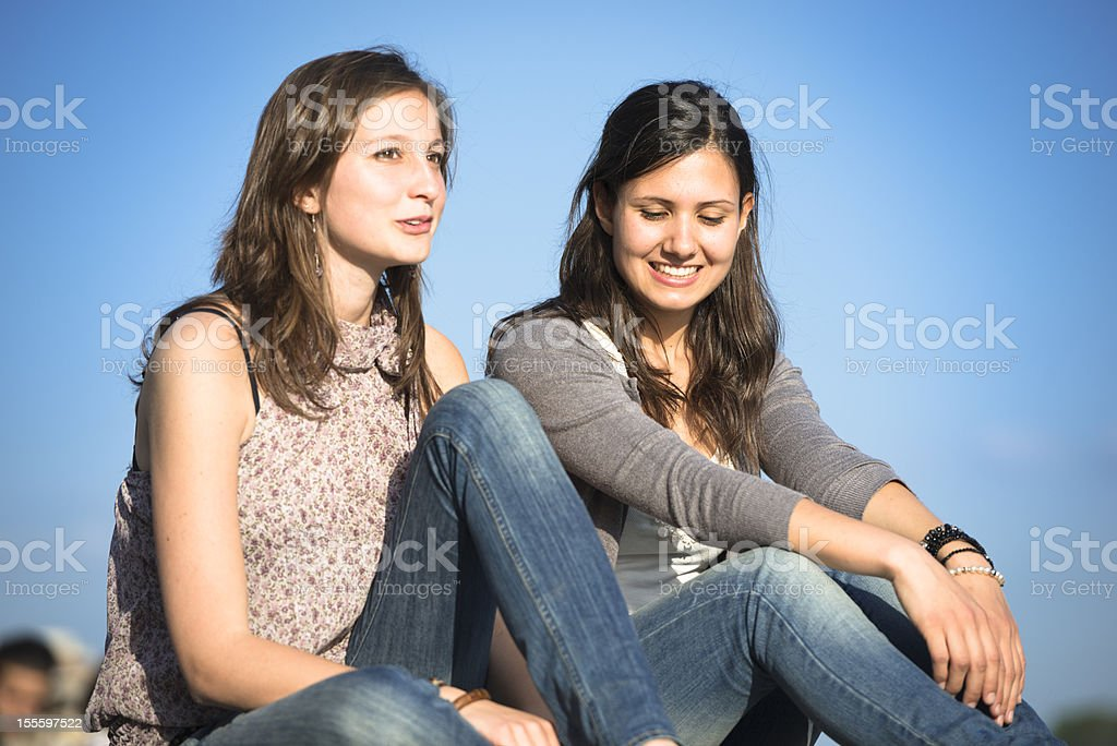 Two friendship laughing sitting together outdoors royalty-free stock photo