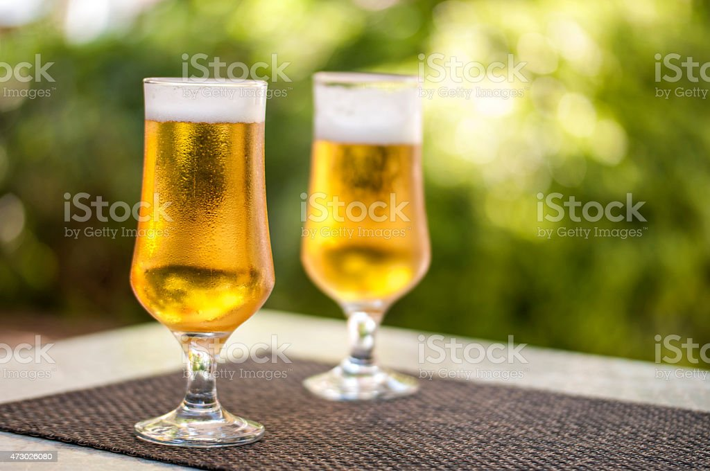 Two full glasses of beer on a patio table stock photo