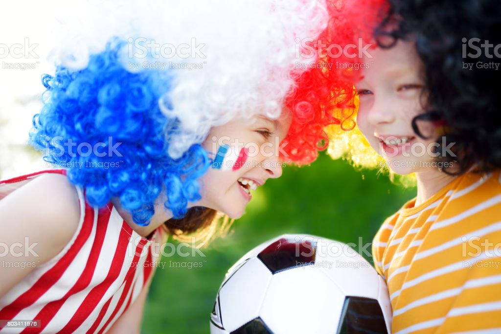 Two funny little sisters supporting and cheering their national football teams stock photo