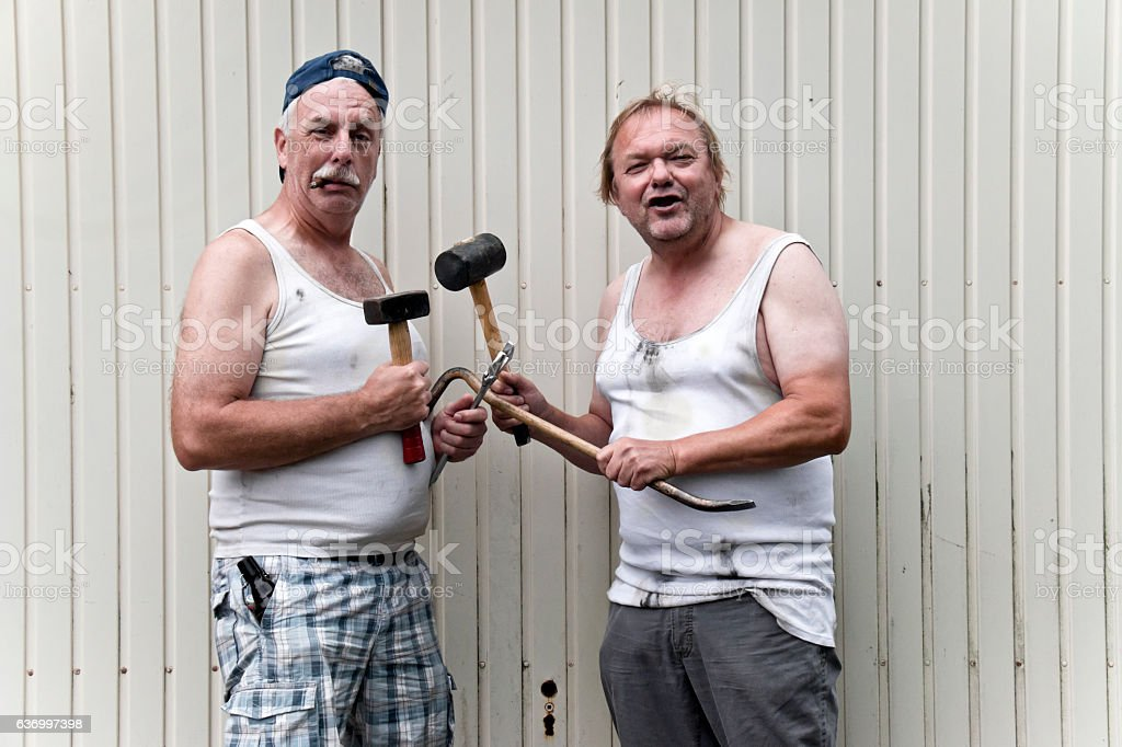 Two funny mechanics with tools stock photo