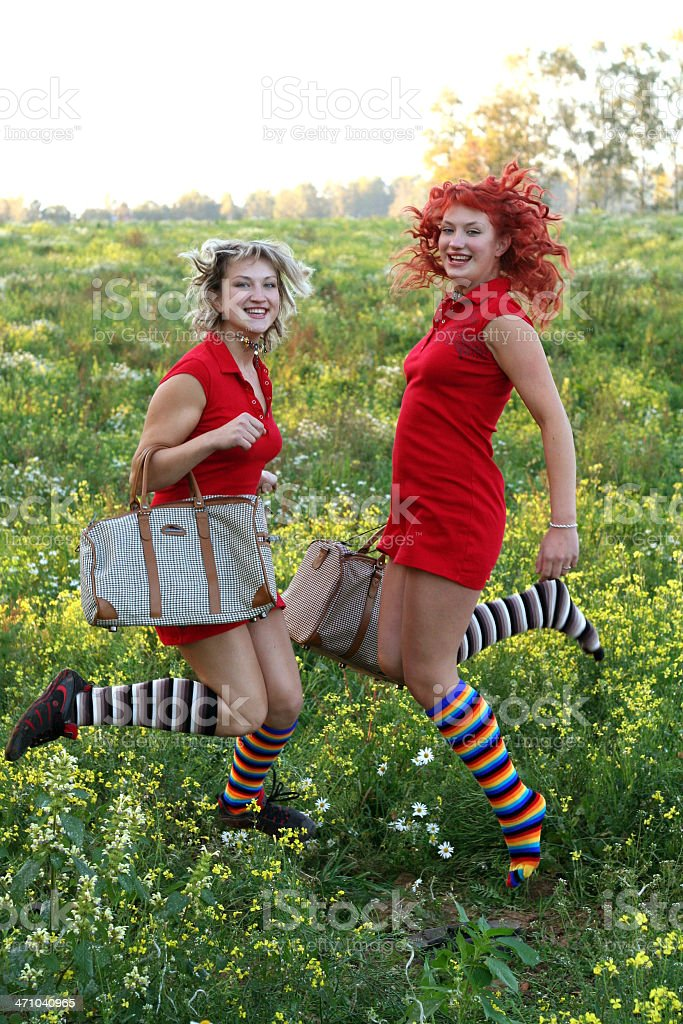 two funny sisters jumping with bags stock photo