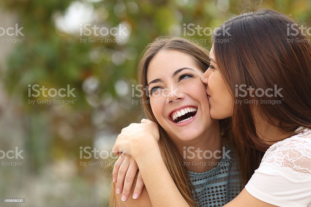 Two funny women friends laughing and kissing stock photo