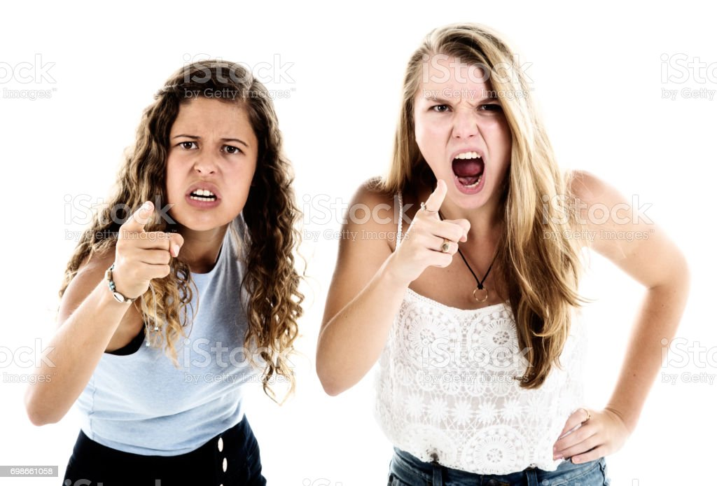 Two furious young women shout and point accusingly stock photo