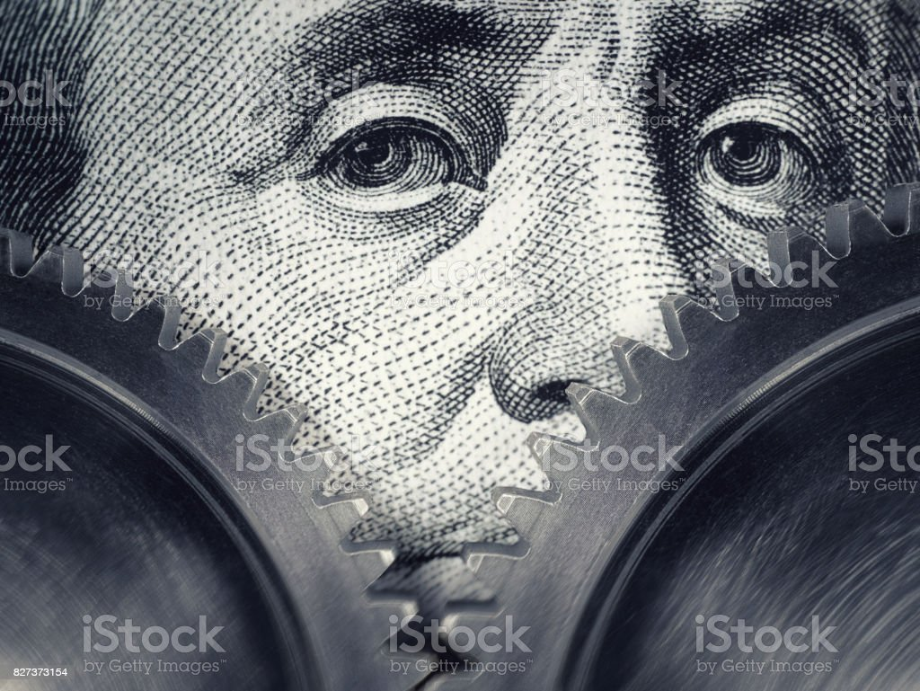 Two gears rotate on the background of hundred dollar bills. stock photo