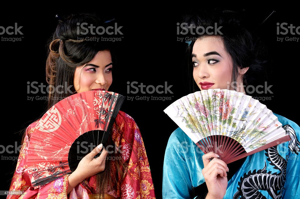 Two geishas exchanging a look behind fans. royalty-free stock photo