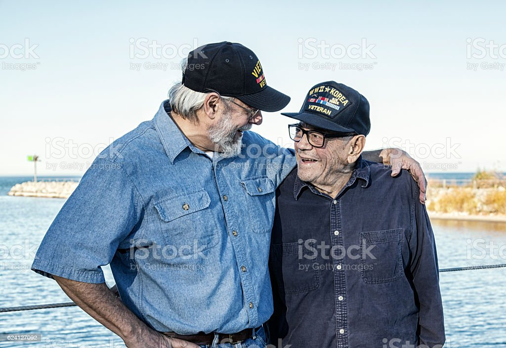 Two Generations of USA Military War Veterans Sharing a Laugh stock photo