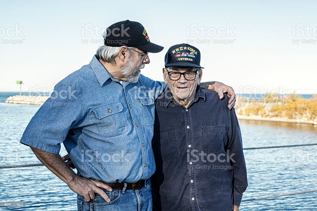 Two Generations of USA Military War Veterans Shooting The Breeze stock photo