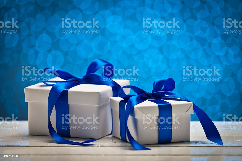 Two gift boxes against blue bokeh lights stock photo