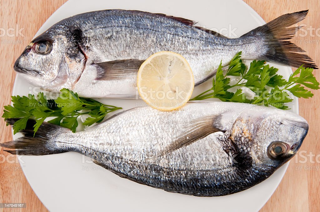 Two Gilthead with slice of lemon and parsley on plate royalty-free stock photo
