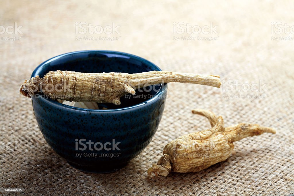 Two ginseng roots one in bowl the other in sack-like surface stock photo