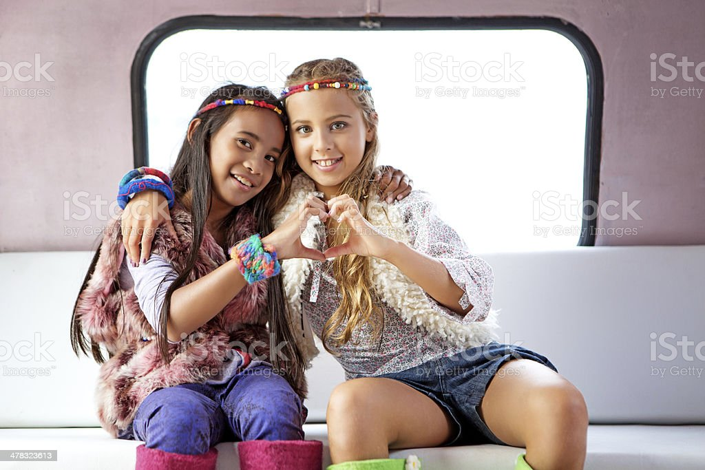 two gipsy girls showing a heart shape royalty-free stock photo